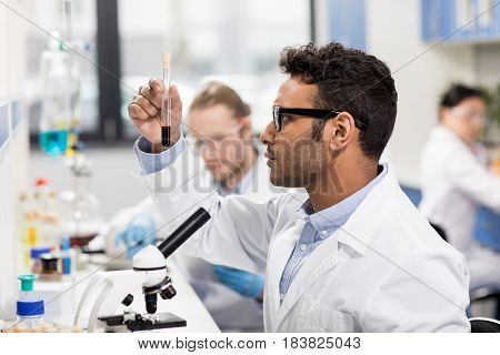 Side view of young scientist in eyeglasses looking at test tube in research laboratory