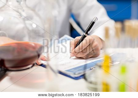 Partial View Of Scientist Writing In Notepad In Laboratory
