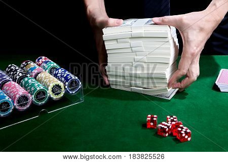 Two hands putting stack of dollars for betting with a card on green table and has chips in box set placed near red dice casino concept