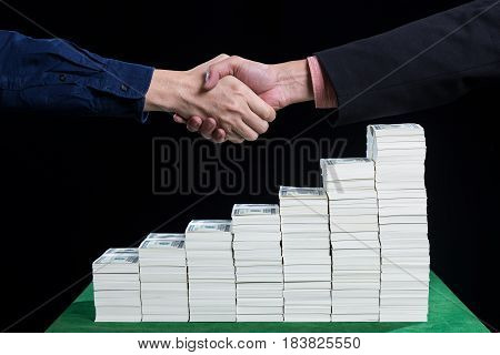 Two businessman shaking hand above the stack of dollars in increasing steps on black background concept business collaboration