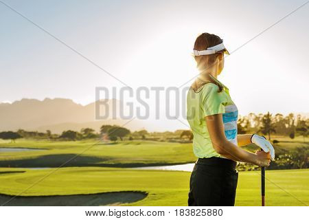 Rear view of young woman standing on golf course on a sunny day. Professional female golfer holding golf club on field and looking away.