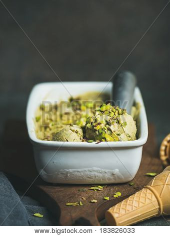 Homemade pistachio ice cream in ceramic mold with metal scooper, crashed pistachio nuts and waffle cones over concrete background, copy space, vertical composition, selective focus