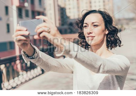 The Girl Poses On The Phone, Photos Herself, Makes A Photo For Social Networks.