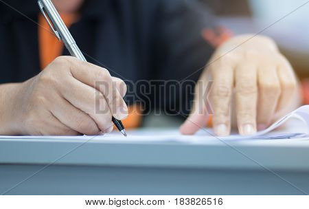 university students hand writing doing examination with blurred abstract background in exam classroom educational college