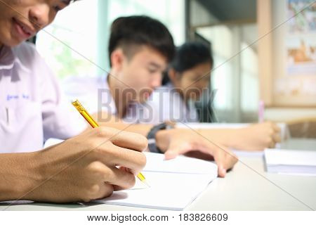 blurred of asia students writing a test in their exercise books on test paper in classroom with uniform