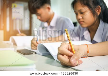 blurred of asian students thai study writing a test in their exercise books on test paper in classroom with uniform