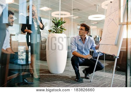 Mature man making a presentation on a flip-chart. Businessman explaining pie chart to colleagues during a meeting.