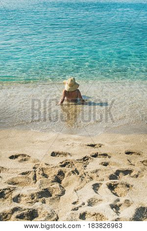 Beautiful slim senior woman tourist in bikini and hat lying on sand enjoying clear sea waters at Meditteranean resort of Turkey in Alanya, Kleopatra beach, rear view