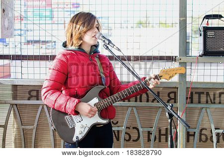 April 20 2017. A street musician girl plays the guitar in the transition in a warm red jacket.