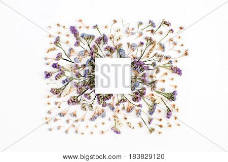 Empty white paper blank on blue and purple dried flowers frame on white background. Flat lay top view