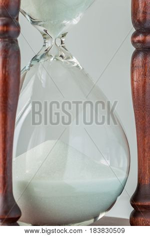 Heap of white sand crystal in vintage wooden hourglass on white background time concept.