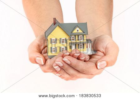 Women's Cupped Hands Holding a Model of a House