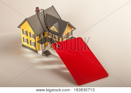 Model of a House with Red Gift Tag on Grey Background