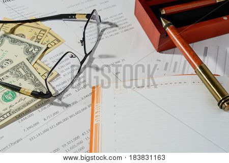 Business documents, financial statistics on the table with money.