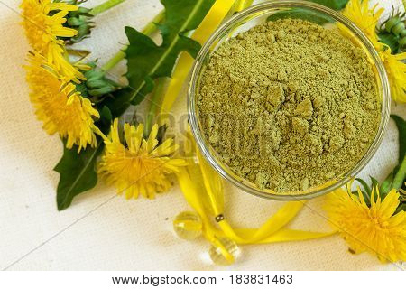 Henna powder. Still life with henna and flowers of dandelions. Focus on the powder.
