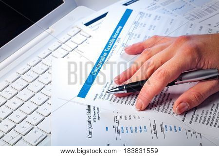 Woman's Hand Holding Pen and Lying on Documents and Laptop