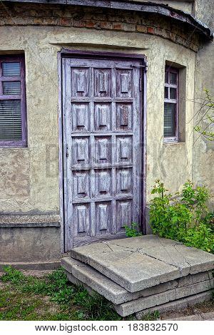 Lilac door on the old wall with windows
