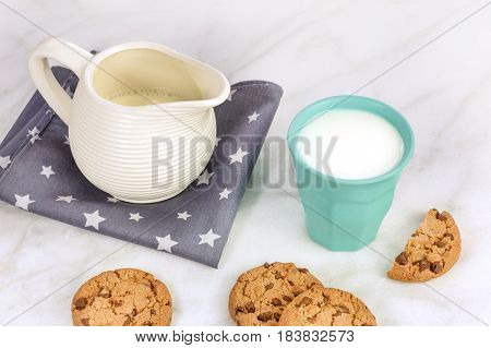 A photo of chocolate chips cookies in front of a glass of milk and a milk jar, with a place for text