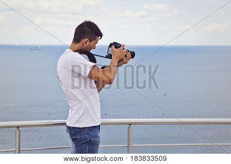 Young attractive man in a white t-shirt with a camera in the sea or ocean beach
