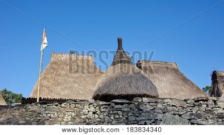 Three grass rooftops and Indonesian flag at Bena a traditional village with grass huts of Ngada people in Flores near Bajawa Indonesia.