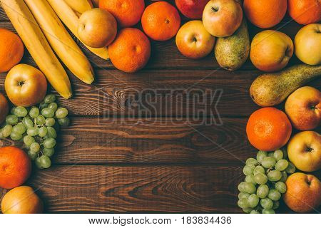 Different fruits as frame on rustic wooden background, top view, copy space for text or recipe. Healthy eating, vegetarian diet concept. Toned image