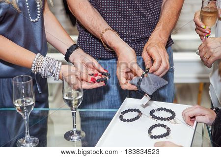 Women try on bracelets and jewelry in a jewelry store