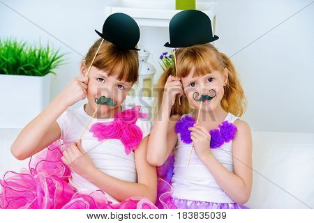 Two little girls sisters playing together with masks. Happy family concept.