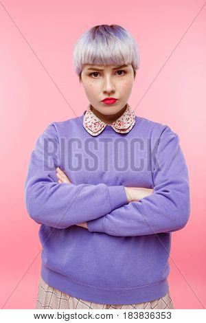 Fashion close-up portrait of confident beautiful dollish girl with short light violet hair wearing lilac sweater over pink background. Copy space.
