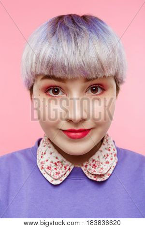 Fashion close-up portrait of smling beautiful dollish girl with short light violet hair wearing lilac sweater over pink background. Copy space.