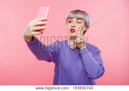 Close-up portrait of beautiful dollish girl with short light violet hair wearing lilac sweater making selfie over pink background. Copy space.