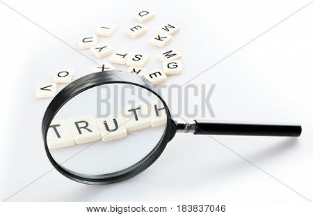 Loupe and Alphabet Tiles Arranged in a Word Truth
