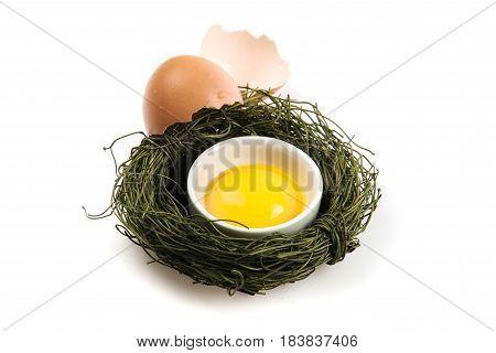 Broken Egg And Yolk In Sauce Cup In Bird Nest