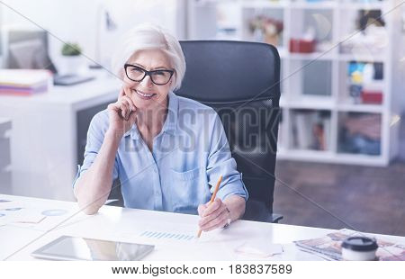 Waiting for tasks. Positive delighted woman keeping smile on her face leaning on her hand while looking straight at camera