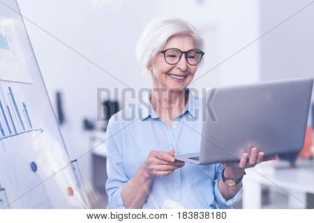 Video conversation. Positive delighted mature female wearing glasses holding laptop in both hands while standing near board