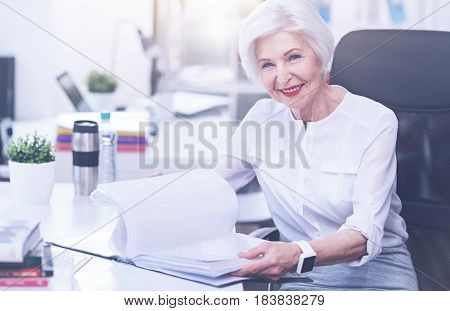 My business. Attractive woman keeping smile on her face holding documents in both hands, sitting on big office chair