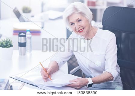 Enjoy your life. Pretty female keeping smile on her face holding pencil in right hand while going to make notes in documents