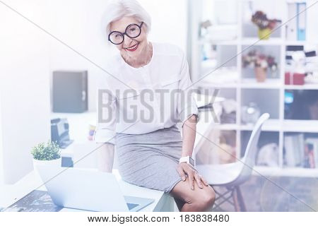 Believe in yourself. Attractive smiling female sitting on the table putting her left hand on the knee while looking forward