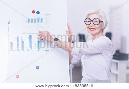 Look here. Amazing blonde woman made her lips red standing near the board while posing on camera