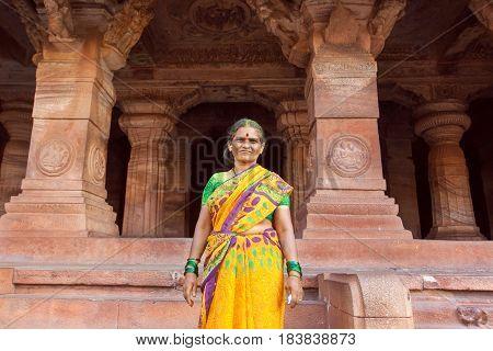 BADAMI, INDIA - FEB 10, 2017: Older woman smiling inside the 6th century Hindu temple with carved columns of ancient Karnataka on February 10, 2017. Population of Karnataka state is 62000000 people