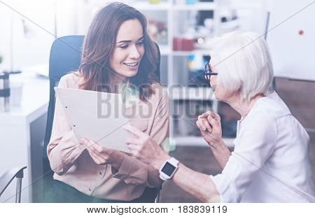 Do not worry. Positive delighted brunette sitting in office chair keeping her mouth opened while speaking with her boss
