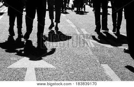 Shadows of people walking in crowded city street