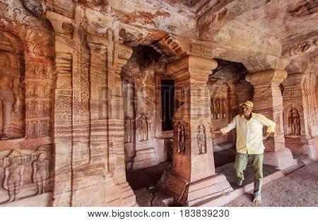 BADAMI, INDIA - FEB 10, 2017: Lonely man watching reliefs inside the 6th century Hindu temple with carved columns of ancient Karnataka on February 10, 2017. Population of Karnataka state is 62000000