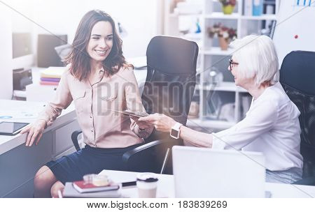 Give it to me. Attractive brunette female keeping smile on her face holding right arm on the table while looking at her instructor