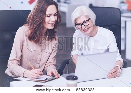 Try to understand. Very attentive smiling young woman looking at the laptop making some notes while sitting near her tutor