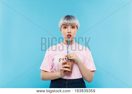 Close up portrait of beautiful dollish girl with short light violet hair in pink tshirt drinking juice over blue background. Copy space.