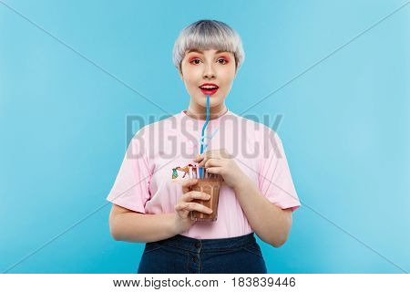 Close up portrait of cheerful smiling beautiful dollish girl with short light violet hair in pink tshirt drinking juice over blue background. Copy space.