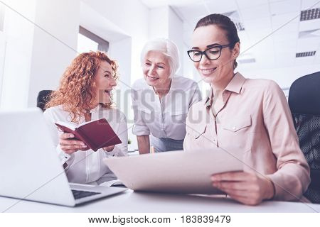 Keep your smile. Attractive brunette sitting on the foreground holding document in left hand while looking at this