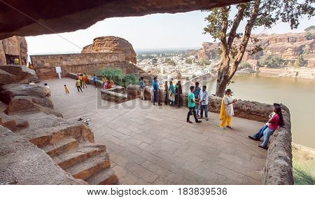 BADAMI, INDIA - FEB 10, 2017: Many people walking around the 6th century Hindu cave temples near a lake of ancient Karnataka on February 10, 2017. Population of Karnataka state is 62000000