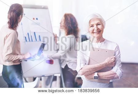 In process. Positive mature female worker standing on the foreground, embracing folder with documents while looking straight at camera