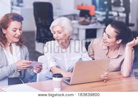 Good result. Amazing blonde woman keeping smile on her face keeping hands on the laptop while looking at business card